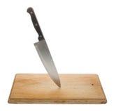 Kniv på en gammal träskärbräda Royaltyfri Bild