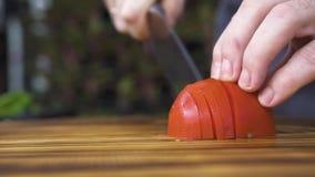 Kniv som ombord skivar den nya tomaten tätt upp Händer av kockkocken som klipper tomaten för pizza Ny ingrediens för stock video