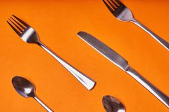 Knivar, skedar och gafflar lade ut p? en orange bakgrund royaltyfria bilder