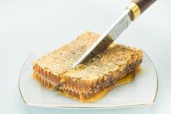 Kniven klipper ett stycke av honungskakor arkivbild