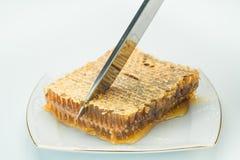 Kniven klipper ett stycke av honungskakor arkivfoton