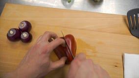 Kniven klipper röd spansk peppar på träskärbräda gem Bitande kärna i söt peppar på träskärbräda remove royaltyfri foto