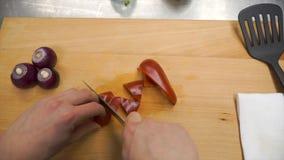 Kniven klipper röd spansk peppar på träskärbräda gem Bitande kärna i söt peppar på träskärbräda remove royaltyfri fotografi