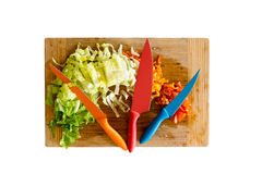 Knives on Cutting Board with Chopped Veggies Royalty Free Stock Photo