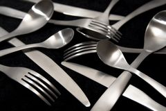 Knives Forks and Spoons. On a black background royalty free stock image