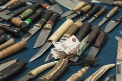 Knives hunting and Russian money rubles. Purchase of cutting wea royalty free stock images