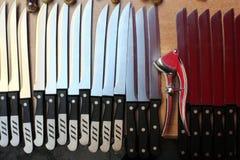 Knives in a row creating a rhythm broken by the garlic press stock photos