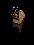 Knives in Wooden Holder on Black. Set of chef's kitchen knives in a wooden holder on black background with reflection Royalty Free Stock Photo