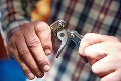Knivmultitool som vänds in i plattång i händerna royaltyfri fotografi