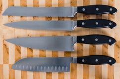 Knivuppsättning på en skärbräda Arkivfoto
