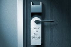 A knob of a hotel door with `Please do not disturb` tag stock photos