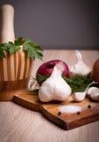 Knoblauch, frische Kräuter der Zwiebel auf altem hölzernem Brett Lizenzfreies Stockbild