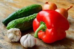 Knoblauch, Gemüsepaprika, Gurken und Zwiebeln auf einem alten Holztisch Lizenzfreie Stockfotos