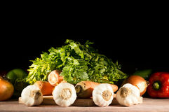 Knoblauch, Karotten, Zwiebeln, Pfeffer und Petersilie gruppiert auf Holztisch Lizenzfreies Stockfoto