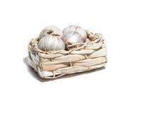 Knoblauch lokalisiert auf Weiß in einem Korb Lizenzfreies Stockfoto