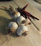 Knoblauch mit Paprikas auf Holztisch Lizenzfreies Stockfoto