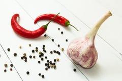 Knoblauch, Pfeffer des roten Paprikas und wohlriechende Mischung von Pfeffern auf einem wei?en Holztisch, w?rziges und dem Backen stockbild