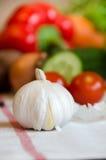 Knoblauch und Gemüse auf einer weißen Tischdecke stockbild
