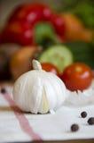 Knoblauch und Gemüse auf einer weißen Tischdecke Lizenzfreies Stockfoto