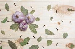 Knoblauch und Lorbeerblatt auf Holztisch lizenzfreies stockfoto