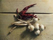 Knoblauch und Paprikas auf hölzernem Brett Stockfotografie
