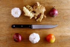 Knoblauch, Zwiebel, Ingwer, Tomate und Messer auf einem hackenden Brett Stockbilder
