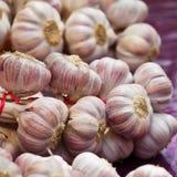 Knoblauchbündel in einem Markt Stockbild