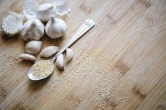 Knoblauchknollen, Nelken und Knoblauchpulver auf einem hölzernen Hintergrund stockbilder