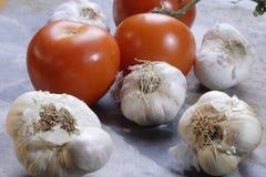 Knoblauchnelken und -tomaten Stockfotos