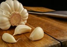 Knoblauchsegmente auf einer Küche verschalen mit einem Messer Stockfotografie