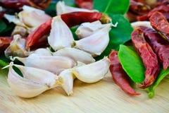 Knoblauchzehen, trockener Paprika, Bergamotte lässt Pfeffer auf hölzernem cutti Lizenzfreie Stockfotos