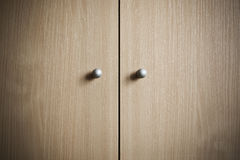 Knobs. Two metal knobs on a wooden cabinet Stock Photography