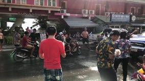 KNOCK-OUT CHANG, THAILAND - APRIL 13, 2018: Songkran festival - folk som besprutar vatten på de, också genom att använda hinkar m lager videofilmer