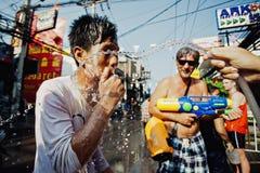 KNOCK-OUT SAMUI, THAILAND - APRIL 13: Den oidentifierade mannen och vatten strömmar på den Songkran festivalen arkivfoto