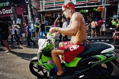 KNOCK-OUT SAMUI, THAILAND - APRIL 13: Oidentifierad smutsig våt cyklist i en vattenkampfestival eller den Songkran festivalen royaltyfria bilder
