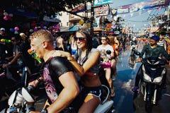 KNOCK-OUT SAMUI, THAILAND - APRIL 13: Oidentifierade våta lyckliga turister på en cykel på den Songkran festivalen Fotografering för Bildbyråer
