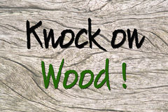 Knock on wood on wood. Text knock on Wood saying on a wooden background stock photography