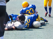 Knocked down athletes Stock Images