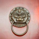 Knocker двери собаки или льва Foo на двери красного цвета Пекина Стоковая Фотография