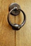 Knocker. Brass knocker on natural wooden door Royalty Free Stock Image