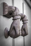 Knocker hand. Rusty hand shaped knocker in an old door. Defocused blurry background Royalty Free Stock Photos
