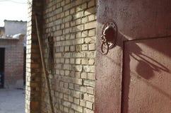 A knocker. An iron knocker of an ordinary countryard's gate stock photography