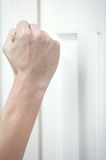 Knocking at the door. Human hand knocking at the wooden door Royalty Free Stock Photography