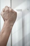 Knocking at the door. Human hand knocking at the wooden door Stock Photography
