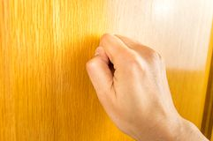 Knocking at the door. Profile view of hand knocking the wooden door Stock Images