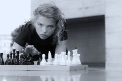 She knocks the board chess pieces Stock Photos