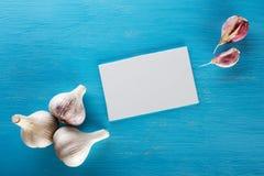 Knoflook en leeg blad voor ingangen op blauwe houten lijst Stock Foto