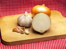 Knoflook en onionon een lijst met een rood tafelkleed Stock Foto