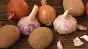 Knoflook en ui, aardappels op scherpe raad stock videobeelden