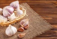 Knoflook horizontale banner Eco de landbouwconcept Gehele garlics en kruidnagels in stromand op stuk van het ontslaan op bruine h Royalty-vrije Stock Afbeeldingen